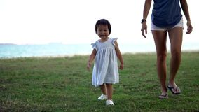 Σε αργή κίνηση της ασιατικής μητέρας και του νέου περπατήματος κοριτσάκι απόθεμα βίντεο