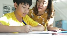 Σε αργή κίνηση της ασιατικής μητέρας με το γιο που κάνει την εργασία σας στο σπίτι με το πρόσωπο χαμόγελου απόθεμα βίντεο