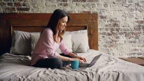 Σε αργή κίνηση της ελκυστικής νέας γυναίκας στα περιστασιακά ενδύματα που δακτυλογραφούν στο lap-top και που χαμογελούν καθμένος  απόθεμα βίντεο