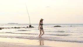 Σε αργή κίνηση της ευτυχούς γυναίκας στο καπέλο που τρέχει στην παραλία κατά τη διάρκεια του ηλιοβασιλέματος στις διακοπές απόθεμα βίντεο