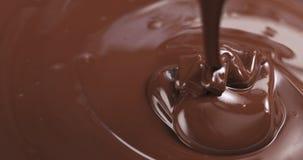 Σε αργή κίνηση της σκοτεινής λειωμένης σοκολάτας ασφαλίστρου που χύνεται από το κουτάλι στο σωστό μέρος του πλαισίου Στοκ Φωτογραφία