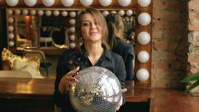 Σε αργή κίνηση της όμορφης νέας γυναίκας με τη σφαίρα disco που θέτει και που χαμογελά στο στούντιο στο εσωτερικό απόθεμα βίντεο