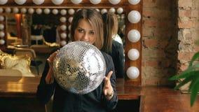 Σε αργή κίνηση της όμορφης νέας γυναίκας με τη σφαίρα disco που θέτει και που χαμογελά στο στούντιο στο εσωτερικό φιλμ μικρού μήκους