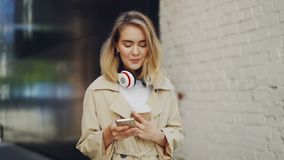 Σε αργή κίνηση του αρκετά νέου smartphone γυναικείας εκμετάλλευσης σχετικά με την οθόνη και τον καφέ κατανάλωσης Τόγκο υπαίθρια l απόθεμα βίντεο