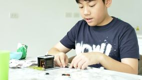 Σε αργή κίνηση του ασιατικού αγοριού που παίζει τον πλαστικό φραγμό στο σπίτι με το πρόσωπο χαμόγελου 4K φιλμ μικρού μήκους
