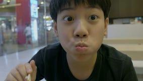 Σε αργή κίνηση του ασιατικού χαριτωμένου αγοριού απολαύστε τα ιαπωνικά τρόφιμα με το πρόσωπο χαμόγελου απόθεμα βίντεο
