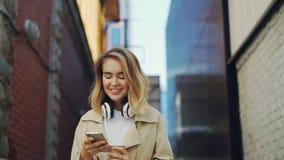 Σε αργή κίνηση του ευτυχούς κοριτσιού που χρησιμοποιεί το smartphone περπατώντας στη φθορά οδών ντύστε και το κράτημα του take-$l φιλμ μικρού μήκους