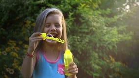 Σε αργή κίνηση του ευτυχούς μικρού καυκάσιου κοριτσιού ένα φυσώντας σαπούνι βράζει μέσα μια ηλιόλουστη ημέρα Παιδική ηλικία ή παι φιλμ μικρού μήκους