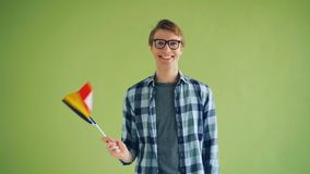 Σε αργή κίνηση του ευτυχούς τύπου που κυματίζει τη γερμανική σημαία που στέκεται στο πράσινο υπόβαθρο απόθεμα βίντεο