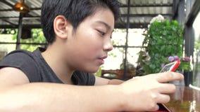Σε αργή κίνηση του νέου ασιατικού παιχνιδιού αγοριών με ένα κινητό τηλέφωνο ή ένα smartphone στον καφέ με το πρόσωπο χαμόγελου απόθεμα βίντεο