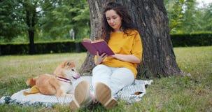 Σε αργή κίνηση του νέου βιβλίου ανάγνωσης γυναικών στη συνεδρίαση πάρκων στο χορτοτάπητα με το σκυλί απόθεμα βίντεο