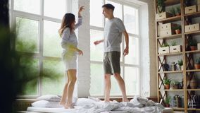 Σε αργή κίνηση του νέου παντρεμένου ζευγαριού που πηδά και που χορεύει στο διπλό κρεβάτι στο ελαφρύ δωμάτιο με τα μεγάλα παράθυρα απόθεμα βίντεο
