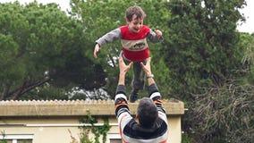 Σε αργή κίνηση του πατέρα που ρίχνει το λατρευτό γιο του στον αέρα απόθεμα βίντεο