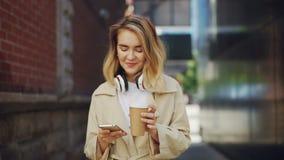 Σε αργή κίνηση του χαμογελώντας κοριτσιού η χρησιμοποίηση του smartphone και η κατανάλωση παίρνουν έξω τον καφέ που στέκεται στην απόθεμα βίντεο
