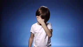 Σε αργή κίνηση του χαριτωμένου μικρού παιδιού που τρίβει τα μάτια του που φωνάζουν ή το κουρασμένο, μπλε υπόβαθρο απόθεμα βίντεο