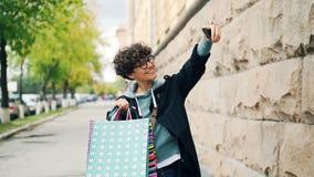 Σε αργή κίνηση του όμορφου κοριτσιού η λήψη selfie με τις αγορές τοποθετεί τη στάση στην οδό, το κράτημα του smartphone και το χα απόθεμα βίντεο