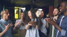 Σε αργή κίνηση του όμορφου κοριτσιού στο κέικ εκμετάλλευσης καπέλων κομμάτων και τα φυσώντας κεριά ενώ οι συνάδελφοι στέκονται γύ απόθεμα βίντεο