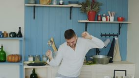 Σε αργή κίνηση του όμορφου νέου αστείου ατόμου που χορεύει και που τραγουδά με την κουτάλα μαγειρεύοντας στην κουζίνα στο σπίτι φιλμ μικρού μήκους