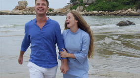 Σε αργή κίνηση το άτομο κρατά το κορίτσι με το χέρι και το φίλημα την Περπατούν κατά μήκος της παραλίας, μιλούν και χαμογελούν απόθεμα βίντεο