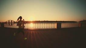 Σε αργή κίνηση: τρέχοντας γυναίκα Ο δρομέας στο ηλιόλουστο φωτεινό φως Θηλυκή πρότυπη κατάρτιση ικανότητας έξω στην πόλη απόθεμα βίντεο