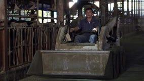 Σε αργή κίνηση τρακτέρ με τον υδραυλικό ανελκυστήρα για τη μεταφορά των δεμάτων του σανού και του χορταριού απόθεμα βίντεο