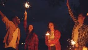 Σε αργή κίνηση των ανδρών και των γυναικών που χορεύουν και που πηδούν υπαίθρια με τα sparklers καψίματος, έχοντας τη διασκέδαση, απόθεμα βίντεο