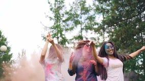 Σε αργή κίνηση των ευτυχών νέων κυριών που χορεύουν στα σύννεφα του χρώματος σκονών ενώ οι άνθρωποι ρίχνουν το ζωηρόχρωμο αλεύρι  απόθεμα βίντεο
