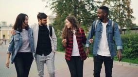 Σε αργή κίνηση των ευτυχών τουριστών φίλων που περπατούν στην οδό που χαμογελά και που μιλά έπειτα να κάνει υψηλός-πέντε τη θεριν απόθεμα βίντεο