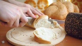 Σε αργή κίνηση των θηλυκών χεριών κόψτε το γαλλικό μαχαίρι ψωμιού απόθεμα βίντεο