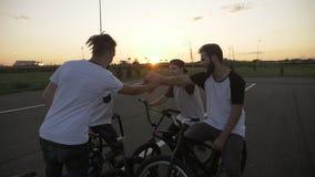 Σε αργή κίνηση των νεολαιών δροσίστε τους ποδηλάτες που κάνουν τα υψηλά fives σχετικά με τις πυγμές τους σε έναν κύκλο ενθαρρυντι φιλμ μικρού μήκους