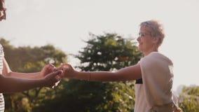 Σε αργή κίνηση χαλαρωμένο ρομαντικό ζεύγος που περπατά μαζί να χορεψει και που χαμογελά το ένα στο άλλο σε ένα όμορφο πάρκο θεριν απόθεμα βίντεο