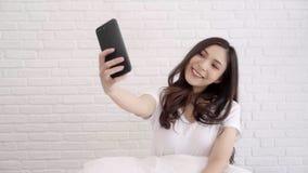 Σε αργή κίνηση - όμορφη νέα ασιατική γυναίκα που χρησιμοποιεί το smartphone για το selfie στο κρεβάτι στην κρεβατοκάμαρά της απόθεμα βίντεο
