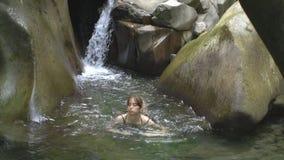 Σε αργή κίνηση όμορφη νέα ελκυστική γυναίκα που κολυμπά στο νερό στη λίμνη βουνών στο πράσινο τροπικό δάσος με τον καταρράκτη φιλμ μικρού μήκους