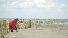 Σε αργή κίνηση όμορφου ξανθού σε ένα φόρεμα που χορεύει κοντά στις ξύλινες θέσεις στη μέση της εκβολής ανάμεσα εγκαταλειμμένος απόθεμα βίντεο