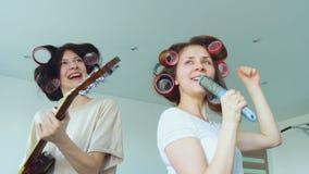 Σε αργή κίνηση δύο αστείων κοριτσιών που τραγουδούν με τη χτένα και τον παίζοντας ηλεκτρικό χορό κιθάρων και τραγουδήστε φιλμ μικρού μήκους