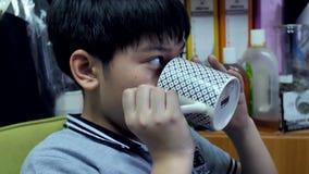 Σε αργή κίνηση 4K ευτυχές ασιατικό πόσιμο νερό αγοριών από το άσπρο φλυτζάνι απόθεμα βίντεο