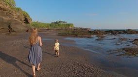 Σε αργή κίνηση steadicam που πυροβολείται μιας οικογένειας που περπατά σε μια δύσκολη ακτή σε έναν ναό μερών Tanah στο νησί του Μ φιλμ μικρού μήκους