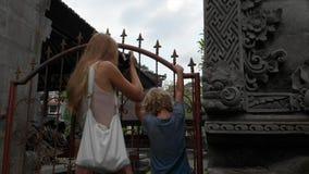 Σε αργή κίνηση steadicam που πυροβολείται της νέων γυναίκας και hel littl του γιου που περπατούν γύρω από το ναό Pura Gunung Leba φιλμ μικρού μήκους