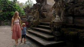 Σε αργή κίνηση steadicam που πυροβολείται της νέων γυναίκας και hel littl του γιου που περπατούν γύρω από το ναό Pura Gunung Leba απόθεμα βίντεο