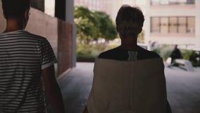 Σε αργή κίνηση sulhouettes του ευτυχούς ρομαντικού ζεύγους που περπατά μαζί να κρατήσει τα χέρια κατά μήκος της οδού πόλεων σε μι απόθεμα βίντεο