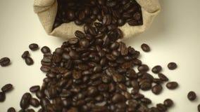 ΣΕ ΑΡΓΗ ΚΊΝΗΣΗ: Πτώσεις σάκων και μια πτώση φασολιών καφέ έξω απόθεμα βίντεο