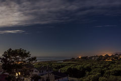 Σεληνόφωτο, αστέρια, σκούρο μπλε ουρανός, και άσπρα σύννεφα Στοκ Εικόνα