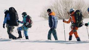 Σε μια γραμμή υπάρχει μια ομάδα καλά εκπαιδευμένων ορειβατών, στηρίζονται στους πόλους σκι και καταβάλλουν προσπάθειες να μην περ απόθεμα βίντεο