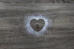 Σε μια ξύλινη σκόνη αλευριού υποβάθρου η σκόνη κάλυψε με μια σκιαγραφία της καρδιάς και βρίσκεται ένα γαμήλιο δαχτυλίδι με ένα δι Στοκ Εικόνες