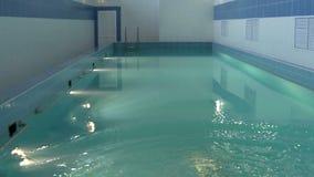 Σε μια ομάδα του γαλαζωπός-πράσινου νερού ένας νέος κολυμβητής βουτά φιλμ μικρού μήκους