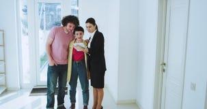 Σε μια φωτεινή σύγχρονη γυναίκα κτηματομεσιτών σπιτιών που παρουσιάζει στο σπίτι στο ελκυστικό νέο ζεύγος πελατών τους τους απόθεμα βίντεο