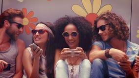 Σε υψηλό - φίλοι ποιοτικού σχήματος hipster που χρησιμοποιούν τα τηλέφωνά τους απόθεμα βίντεο