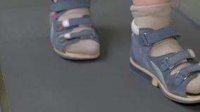 Σε Nea Kallikratia, η Ελλάδα στο μικρό παιδί κλινικών περπατά αργά ιατρικό treadmill με μια ηλεκτρονική συσκευή στα πόδια φιλμ μικρού μήκους
