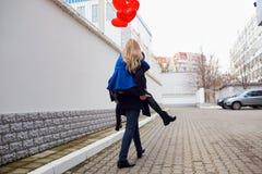 Σηκώνω στην πλάτη κοριτσιών στον τύπο με τα κόκκινα μπαλόνια καρδιών στην οδό Στοκ φωτογραφία με δικαίωμα ελεύθερης χρήσης