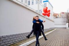 Σηκώνω στην πλάτη κοριτσιών στον τύπο με τα κόκκινα μπαλόνια καρδιών στην οδό Στοκ φωτογραφίες με δικαίωμα ελεύθερης χρήσης